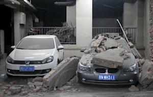 Damaged cars and broken wall are pictured inside the…