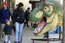 "A woman and child pass a prop from the movie ""Jurassic Park"" on a New York street on December 20, 20.."