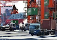 Containers are unloaded from freighters at Tokyo&#39;s port on January 11, 2013. Japan&#39;s hard-charging prime minister said he wanted in on talks to forge a huge trade pact, the latest bold move from a man who says he is determined to lick the frail economy into shape