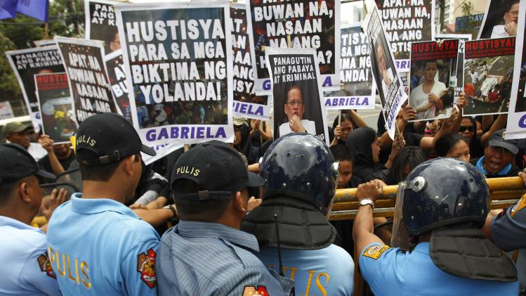 Anti-riot policemen block the women's advocacy group GABRIELA and victims of Typhoon Haiyan during a International Women's Day protest rally outside the residence of President Benigno Aquino in Quezon city, metro Manila