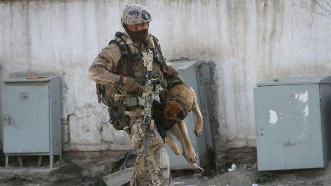 A soldier, part of the NATO forces, carries a sniffing dog after a gun battle in Kabul, Afghanistan, Monday, April 16, 2012. A brazen, 18-hour Taliban attack on the Afghan capital ended early Monday when insurgents who had holed up overnight in two buildings were overcome by heavy gunfire from Afghan-led forces and pre-dawn air assaults from U.S.-led coalition helicopters. (AP Photo/Musadeq Sadeq)