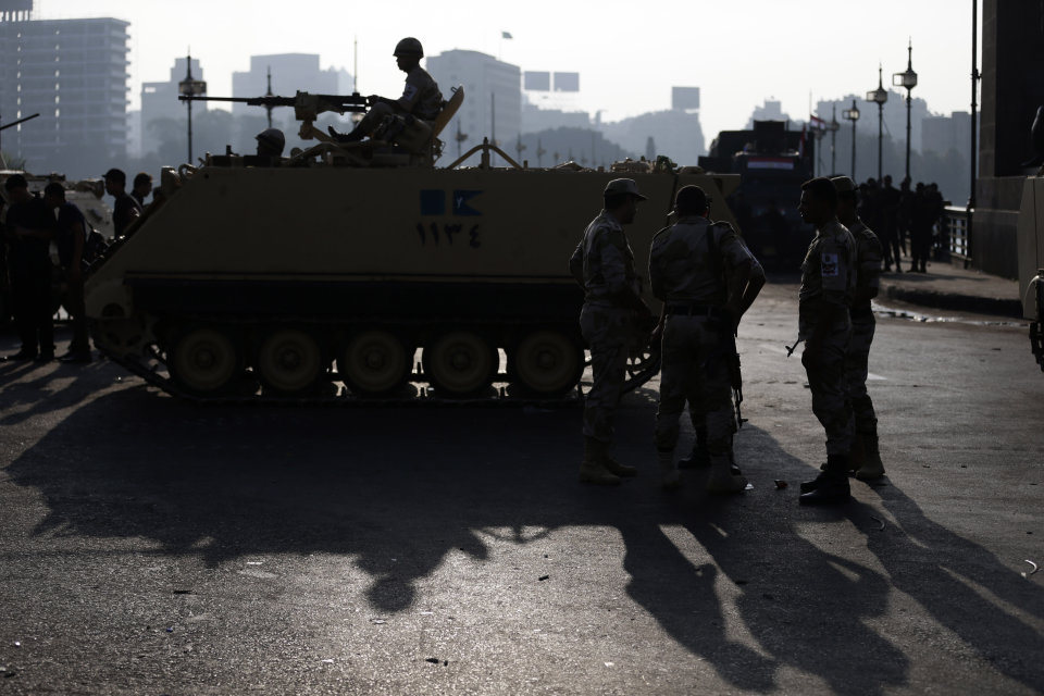 Egyptian army soldiers take their positions near armored vehicles to guard the entrances of Tahrir square, in Cairo, Egypt, Monday, July 8, 2013. Egyptian military officials said gunmen killed at least five supporters of the former president when people tried to storm a military building in Cairo. The official, who declined to be named because he was not authorized to brief reporters, also said a group had tried to storm the headquarters of the Republican Guard. He added that those killed had been supporters of former President Mohammed Morsi camped outside the building in protest at his overthrow. (AP Photo/Hassan Ammar)