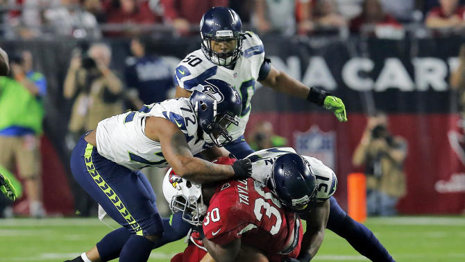 Arizona Cardinals running back Stepfan Taylor (30) is stopped by Seattle Seahawks defensive end Michael Bennett (72) and Bruce Irvin during the first half of an NFL football game, Sunday, Dec. 21, 2014, in Glendale, Ariz. (AP Photo/Rick Scuteri)