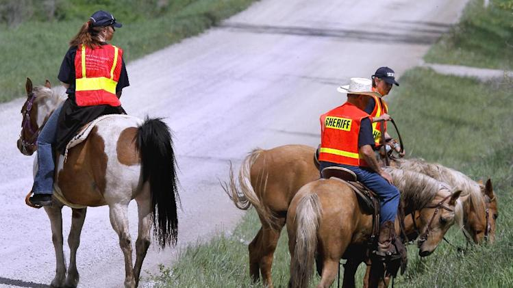 Law enforcement officials search the surrounding area of a farm in rural Ottawa, Kan., on horseback Thursday May 9, 2013, for a baby belonging to one of the victims of Monday's triple homicide. Authorities in eastern Kansas said Thursday they have arrested a 27-year-old suspect in the deaths of three people whose bodies were found at a farm, and that a fourth victim — an 18-month-old girl — is presumed dead. (AP Photo/The Topeka Capital Journal, Chris Neal)