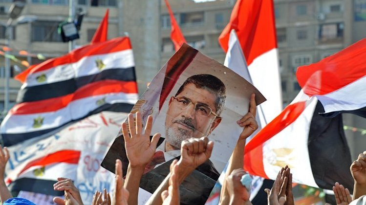 Muslim Brotherhood supporters hold a portrait of Mohamed Morsi during a rally in Cairo, on July 24, 2013