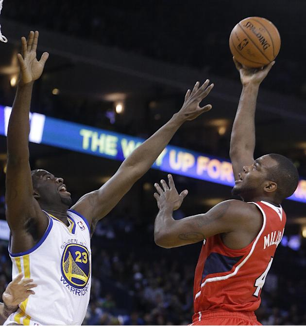 Atlanta Hawks' Paul Millsap, right, shoots over Golden State Warriors' Draymond Green (23 during the first half of an NBA basketball game Friday, March 7, 2014, in Oakland, Calif