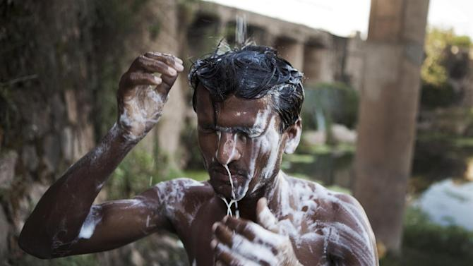 A man showers under a broken pipeline during a hot afternoon as temperature rose to 111 degrees Fahrenheit (44 degrees Celsius) in the suburbs of Islamabad, Pakistan, Thursday, June 21, 2012. (AP Photo/B.K. Bangash)