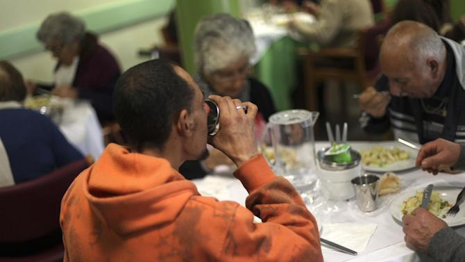Felipe Valadas, 35, who is unemployed, drinks while he has a meal with other people in the eating hall of the Portuguese Catholic charity organization Santa Casa da Misericordia in Lisbon, Wednesday, Feb. 20, 2013. Valadas, whose cleaning company closed down two-years ago, doesn't get any unemployment benefits and has been receiving free daily meals for seven months. (AP Photo/Francisco Seco)