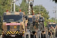 "A Turkish army convoy drives to the Syrian border. Rebels have moved their command base from Turkey to ""liberated areas"" inside Syria, they announced on Saturday as regime troops and rebels battled for control of a corridor near the border"