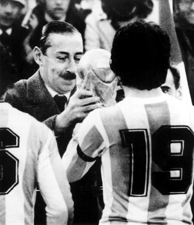 Jorge Rafael Videla (L) presents the World Cup trophy to Argentine national soccer team captain Daniel Passarella
