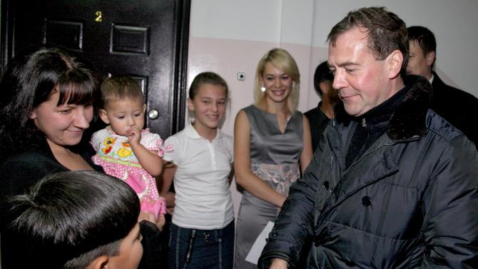 Russian President Dmitry Medvedev, right, shakes hands with a boy as he visits a family in the town of Yuzhnokurilsk, at the Pacific Island of Kunashir, Russia, Monday, Nov. 1, 2010. Medvedev landed on Kunashiri Island, known in Russian as Kunashir, just off the Japan's northern coast, triggering immediate protests from Tokyo. (AP Photo/RIA-Novosti, Mikhail Klementyev, Presidential Press Service)