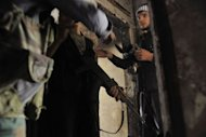 Syrian rebels take position inside a house during clashes with government forces in the Saif al-Dawla district of the northern city of Aleppo