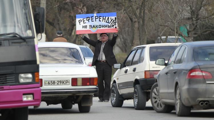 "A man holds placard, which reads: ""The referendum is illegal"", during a pro-Ukrainian rally in Bakhchisaray"