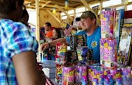 A vendor sells fireworks at a stand in Washington on July 3. More than a million customers in the storm-hit United States remained without power Wednesday, as canceled firework displays and no air-conditioning made for a miserable July 4 holiday for many Americans