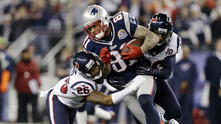 New England Patriots tight end Aaron Hernandez (81) gains yards after a catch against Houston Texans defensive back Brandon Harris (26) and free safety Danieal Manning (38) during the second quarter of an NFL football game in Foxborough, Mass., Monday, Dec. 10, 2012. (AP Photo/Elise Amendola)