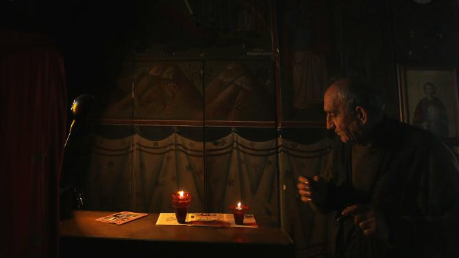 Evangelos, the caretaker of the Greek Orthodox church of Saint George, prepares vigil oil lamps inside the 19th century church atop the Lycabettus hill