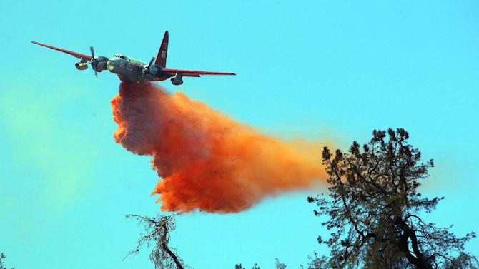 A plane drops water to fight what has been called the Powerhouse fire in the rural community of Lake Hughes in northern Los Angeles County. Calif., Monday, June 3, 2013. At least six houses have been destroyed by the fire, nine more were damaged, and 2,800 people fled 700 homes in Lake Hughes and Lake Elizabeth, 45 miles northwest of downtown Los Angeles. (AP Photo/Nick Ut)