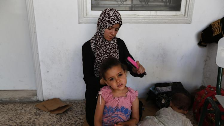 Malak Hijazi 5, has her hair combed by her mother Gaza, as they begin their day on the grounds of the St. Porphyrios Church in Gaza City, Wednesday, July 23, 2014. St. Porphyrios Church has thrown its doors open to hundreds of displaced Palestinians, some of the more than 140,000 who have fled their homes, according to the UN. (AP Photo/Lefteris Pitarakis)