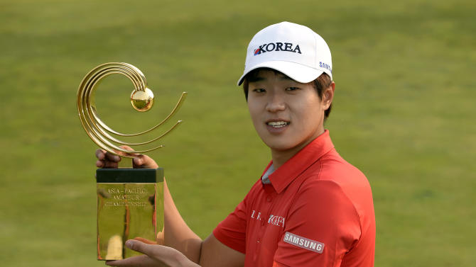 In this photo released by OneAsia, Lee Chang-woo of South Korea poses with the winner's trophy after the final round of the Asia-Pacific Amateur Championship at the Nanshan International Golf Club in Longkou, Shandong Province, China, Sunday, Oct. 27, 2013. (AP Photo/OneAsia, Paul Lakatos) NO LICENSING