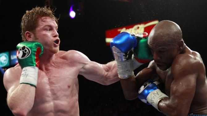 WBC/WBA 154-pound champion Canelo Alvarez punches at Floyd Mayweather Jr. of the U.S. in Las Vegas