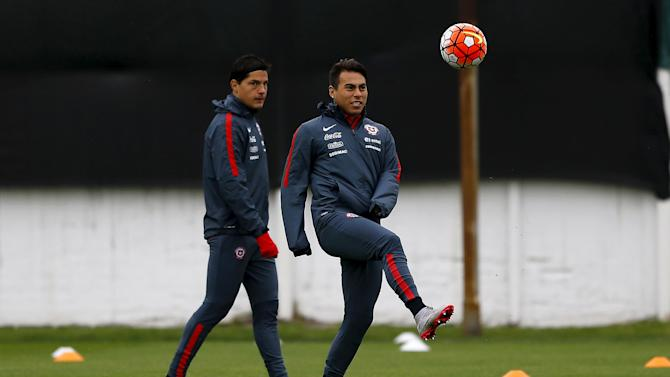 Chile's player Vargas kicks a ball as Albornoz looks on during a team training ahead of their 2018 World Cup qualifying match against Brazil this Thursday session in Santiago