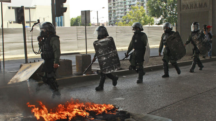 Riot police patrol a street after looting broke out during clashes between protestors and police, in Panama City, Friday, Oct. 26, 2012. Panama's government said Friday it will cancel plans to sell state-owned land in a duty-free zone following a week of sometimes violent protests in which a 10-year-old boy and two adults died. Though the land in question is in the port city of Colon, protests spread to Panama City. (AP Photo/Arnulfo Franco)