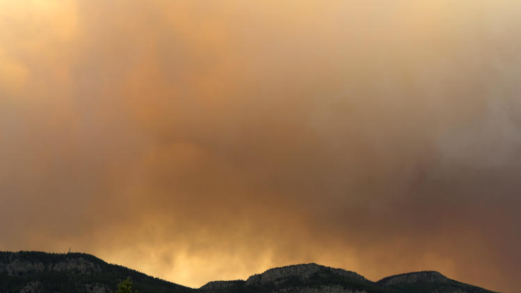 Wildfire smoke blankets a ridge Sunday, June 23, 2013, near Alpine, Colo. A large wildfire near a popular summer retreat in southern Colorado continues to be driven by winds and fueled by dead trees in a drought-stricken area, authorities said Sunday. (AP Photo/Gregory Bull)