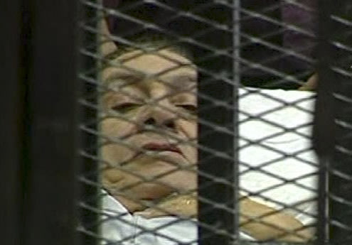 Hosni Mubarak laying on a hospital bed inside a cage of mesh and iron bars. (AP Photo/Egyptian State TV)