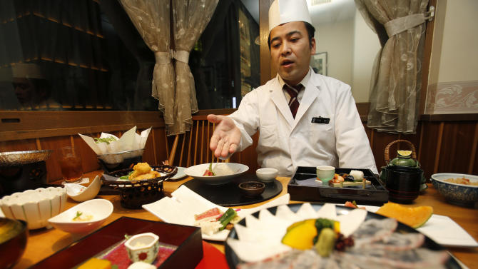 "In this Wednesday, Nov. 27, 2013 photo, chief chef Kenji Uda explains about the menu at Japanese restaurant Irimoya Bettei in Tokyo. Washoku, the traditional cuisine of Japan, is being considered for designation as part of the world's priceless cultural heritage by the U.N. this week. But even as sushi and sake booms worldwide, purists say its finer points are candidates for the endangered list at home. The younger generation is increasingly eating Krispy Kreme donuts and McDonald's, not rice. Uda, 47, says he was 17 when he decided to devote his life to washoku. ""Japanese food is so beautiful to look at,"" he said. ""But it takes a lot of time. People are working and busy, and no longer have that kind of time."" (AP Photo/Shizuo Kambayashi)"