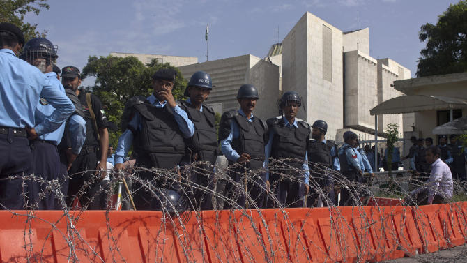 Pakistan's police officers stand guard behind a barbed-wire outside the Supreme Court, where Prime Minister Raja Pervaiz Ashraf, unseen, appears for a hearing in Islamabad, Pakistan on Tuesday, Sept. 18, 2012.  Pakistan's prime minister has agreed to a longstanding Supreme Court demand to reopen a corruption case against the country's president. The decision could defuse tensions over the case that have roiled Pakistan's political system for month and lead to the ouster of the last premier. (AP Photo/Anjum Naveed)