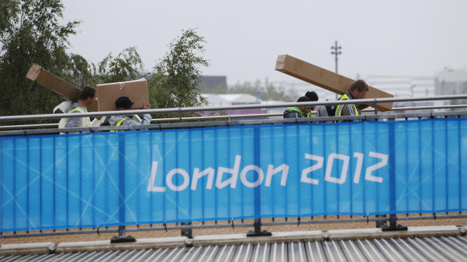 Workers carry packages into the Olympic Park before the start of  the 2012 Summer Olympics, Monday, July 16, 2012, in London. (AP Photo/Jae Hong)