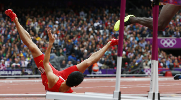 China's Liu Xiang falls onto the track during his men's 110m hurdles round 1 heat at the London 2012 Olympic Games at the Olympic Stadium