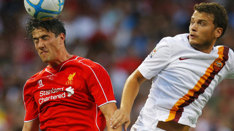 Liverpool's Martin Kelly heads the ball in front of AS Roma's Adem Ljajic during friendly soccer match at Fenway Park in Boston