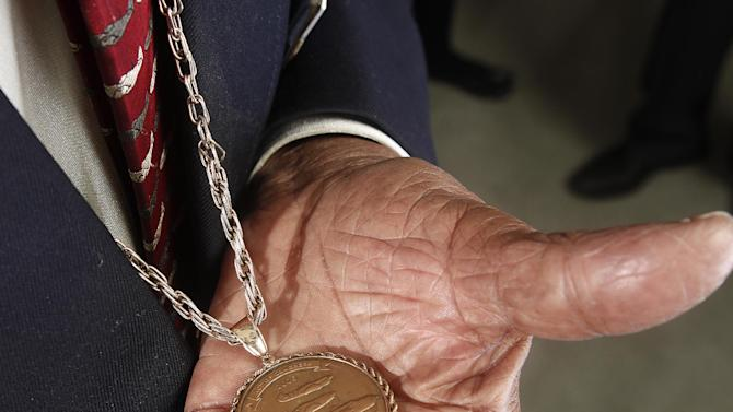 """In this Jan. 10, 2012 photo, Tuskegee airman Floyd Carter Sr. displays his medal during the """"Red Tails"""" press junket in New York.  """"Red Tails,"""" a film that chronicles the heroism of the Tuskegee Airmen, opens Friday, Jan. 20. (AP Photo/Carlo Allegri)"""