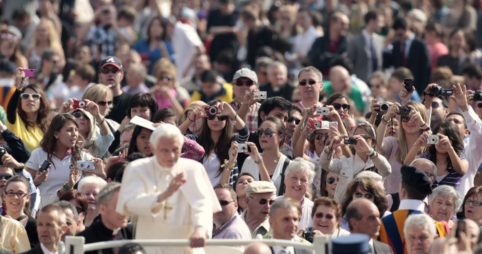Pope Benedict XVI, foreground, is photographed by the faithful as he tours St. Peter's square during the weekly general audience at the Vatican, Wednesday, April 4, 2012. (AP Photo/Gregorio Borgia)