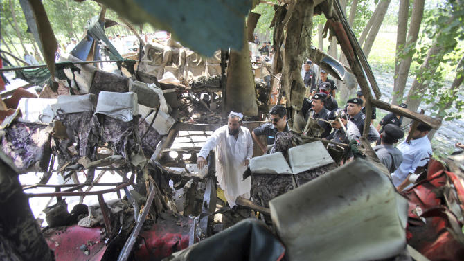 Pakistani police officers check the wreckage of a bus that exploded when a bomb planted in it went off on the outskirts of Peshawar, Pakistan, Friday, June 8, 2012. A bomb tore through a bus carrying government employees and other civilians in northwestern Pakistan on Friday, killing several people in an attack that served as a reminder of the continued militant threat despite a significant drop in violence over the past year, officials said. (AP Photo/Mohammad Sajjad)