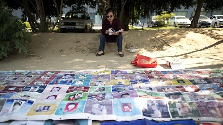 Ye Jinxiu, 59, sits before pictures of missing children on the streets of Fuzhou on China's east coast Fujian province, on October 23, 2013