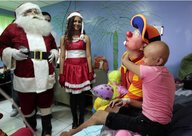 A young cancer patient embraces a clown after receiving a gift at the La Mascota children's hospital in Managua