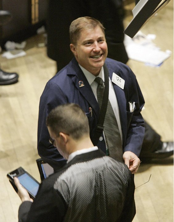 FILE - In this April 25, 2007 file photo, a trader smiles as he works on the floor of the New York Stock Exchange. The stock market's best-known indicator surged past its latest milestone shortly afte