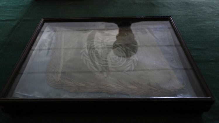 "A shadow of a North Korean soldier is reflected on the United Nations flag, which North Korean military says was hanging during the Korean War Armistice Agreement signing in 1953, placed in a glass case inside a room on the North side at Panmunjom Monday, April 23, 2012. North Korea promised Monday to reduce South Korea's conservative government ""to ashes"" in less than four minutes, in an unusually specific escalation of recent threats aimed at its southern rival. The threat follows U.N. condemnation of the North Korean launch of a long-range rocket that exploded shortly after liftoff on April 13. (AP Photo/Vincent Yu)"