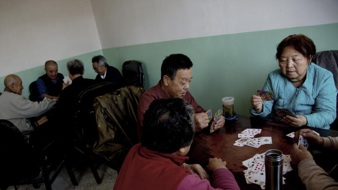 In this photo taken on Wednesday, Oct. 24, 2012, retired employees of a government office play cards at an old hospital administration building in Xilinhot in northern China's Inner Mongolia. Buying and selling office is so rampant in China that it has eroded public trust in officialdom, undermining the ruling Communist Party's image as an institute that promotes the competent, not the connected. Even though Chinese leaders have vowed to eradicate the practice, it has showed no sign of abatement. (AP Photo/Andy Wong)