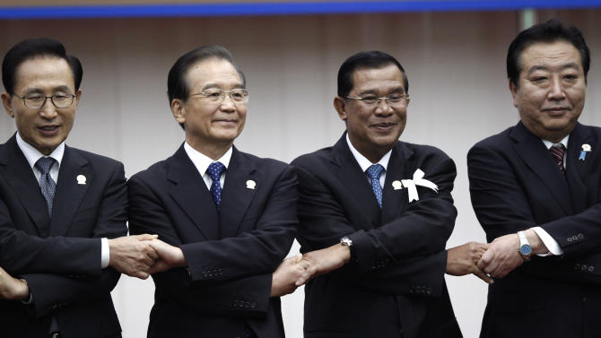 FILE - In this Nov. 19, 2012 file photo,  China's Premier Wen Jiabao, second left, joins hands with South Korea's President Lee Myung-bak, left, Cambodia's Prime Minister Hun Sen, third lfrom eft, and Japan's Prime Minister Yoshihiko Noda during the ASEAN Plus Three (APT) Commemorative Summit in Phnom Penh, Cambodia.  China's finding the once friendly ground of Southeast Asia bumpy going, with anger against Chinese claims to disputed islands, once reliable ally Myanmar flirting with democracy and renewed American attention to the region.  (AP Photo/Vincent Thian, File)