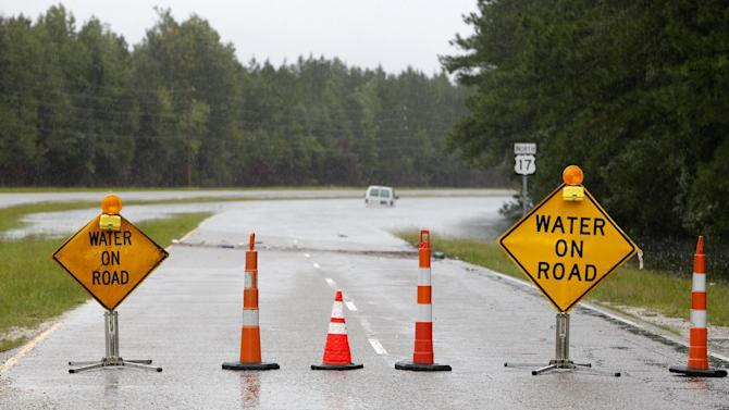 signs block entry to U.S. Hwy. 17 North near Georgetown, S.C., Sunday, Oct. 4, 2015 after vehicles became stuck in floodwaters. Several sections of Highway 17 are shut down between Charleston and Georgetown. (AP Photo/Mic Smith)