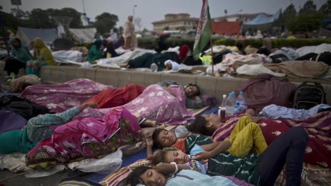 Pakistani children and female protesters sleep in front of the parliament building, during weeklong protests from the eastern city of Lahore to the gates of parliament calling for Prime Minister Nawaz Sharif's ouster over alleged voting fraud, in Islamabad, Pakistan, Friday, Aug. 22, 2014. They swarmed into the capital in their thousands, protesters calling for the prime minister's resignation and the dissolution of parliament. The week-long protests in the capital and around the parliament building have been loud and boisterous but peaceful. But despite their color, there is the other side to the demonstrations _ the increased demand for food, water and toilets to accommodate the thousands of people who turned out to support cricketer-turned-politician Imran Khan and popular cleric Tahir-ul-Qadri. (AP Photo/Muhammed Muheisen)