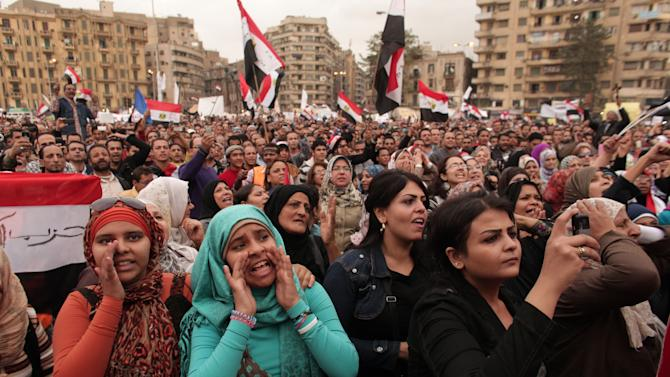 Protesters chant slogans and wave national flags in Tahrir Square in Cairo, Egypt, Tuesday, Dec. 4, 2012. Hundreds of black-clad riot police deployed around the Itihadiya palace in Cairo's district of Heliopolis. Barbed wire was also placed outside the complex, and side roads leading to it were blocked to traffic. Protesters gathered at Cairo's Tahrir square and several other points not far from the palace to march to the presidential complex. (AP Photo/Maya Alleruzzo)