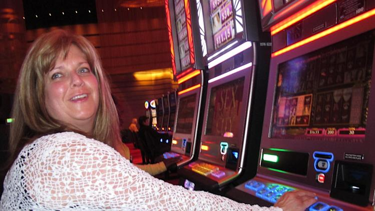 "FILE - In this May 21, 2012 file photo, Donna Kiddie of Point Pleasant Beach N.J. plays a ""Sex And The City"" slot machine at Revel in Atlantic City N.J. Revel, which is in federal bankruptcy court, posted a $110 million operating loss in the nine months it was open in 2012. Atlantic City's 12 casinos collectively posted a $360 million operating profit last year, down 27.5 percent from 2011. (AP Photo/Wayne Parry, File)"