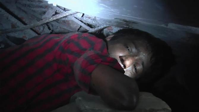 In this image taken from AP video, garment worker Mohammad Altab moans to rescuers for help while trapped between concrete slabs and next to two corpses in a garment factory that collapsed Wednesday in Savar, near Dhaka, Bangladesh, Thursday, April 25, 2013. Deep cracks visible in the walls of the Bangladesh garment building had compelled police to order it evacuated a day before it collapsed, officials said Thursday. More than 200 people were killed when the eight-story building splintered into a pile of concrete because factories based there ignored the order and kept more than 2,000 people working. (AP Photo/AP video)
