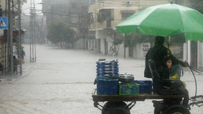 Palestinians ride a donkey cart through a flooded road during heavy rain in Gaza City