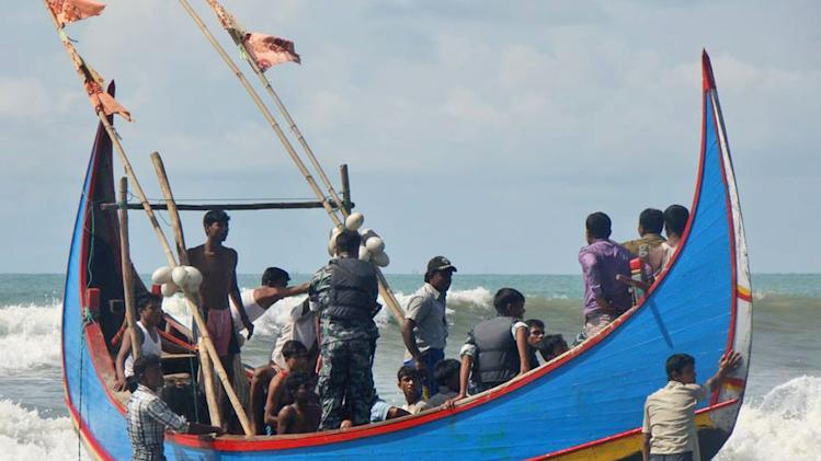 Bangladesh Border Guard soldiers check survivors rescued from a boat capsize in Teknaf, Bangladesh, Wednesday, Nov. 7, 2012. Officials said Wednesday that 23 people were rescued after an overcrowded boat capsized off the Bangladesh coast, but about 50 others remained missing. The boat was reportedly carrying about 70 illegal migrants, mostly Rohingya Muslims, from Myanmar to Malaysia when it sank in the Bay of Bengal early Wednesday. (AP Photo)