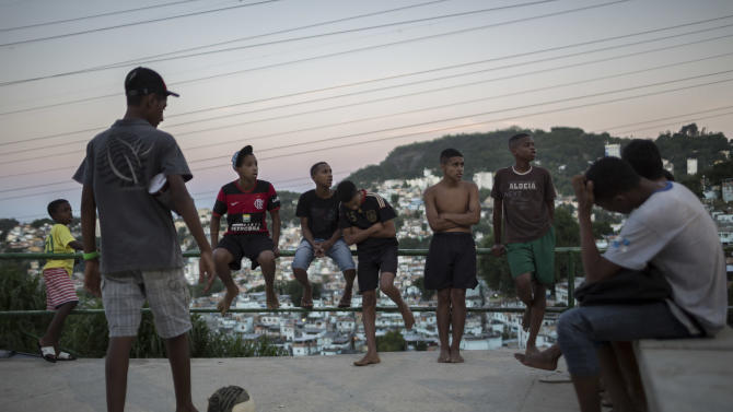 Boys for wait their turn to play soccer at the Sao Carlos slum in Rio de Janeiro, Brazil, Monday, May 12, 2014. As opening day for the World Cup approaches, people continue to stage protests, some about the billions of dollars spent on the World Cup at a time of social hardship, but soccer is still a unifying force. The international soccer tournament will be the first in the South American nation since 1950